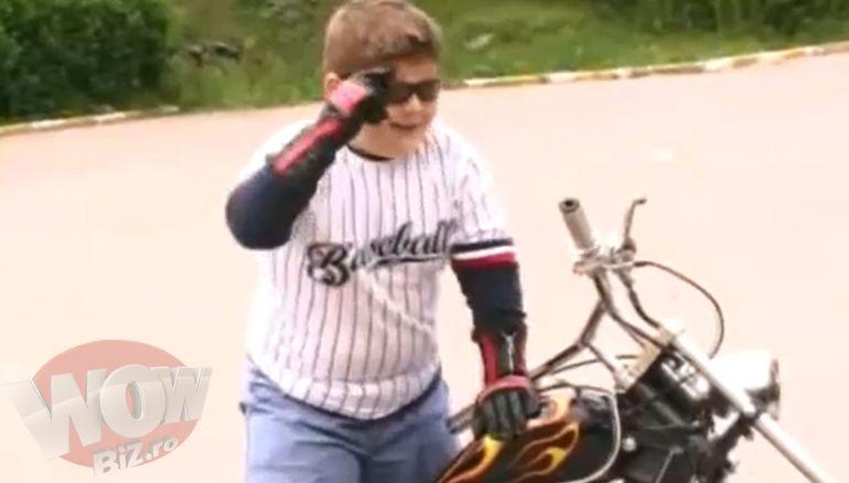 Mai horror nu se poate! Baietelul dolofan al Nicoletei Guta joaca intr-un clip al mamei: merge cu motocicleta, are ghiuluri pe degete si cercel in ureche, trage cu pistolul si se culca intr-un pat roz!