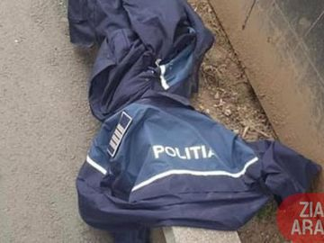 Fotografia din Arad care a devenit virală pe net! Haine de polițiști, purtate de boschetari și aruncate pe stradă