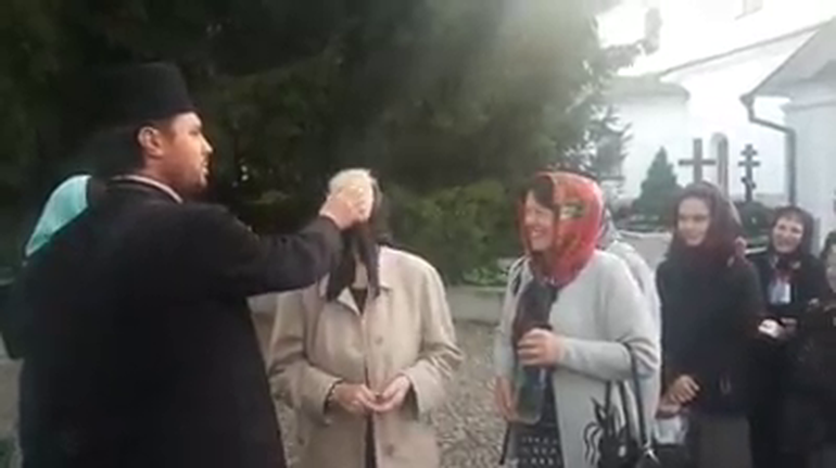 VIDEO viral! Un preot sfințește credincioșii aruncându-le cu agheasmă direct în ochi. Toată lumea se prăpădește de râs la coadă la binecuvântare