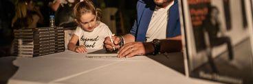 Florin Dumitrescu, ajutat să dea autografe de  fetițele sale, Ava și Mia