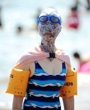 Astra-i ultima moda in China! Motivul pentru care femeile isi acopera fata cu masti colorate pe plaja
