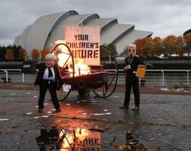 Un bărbat deghizat în Boris Johnson a protestat în fața centrului care a găzduit COP26....