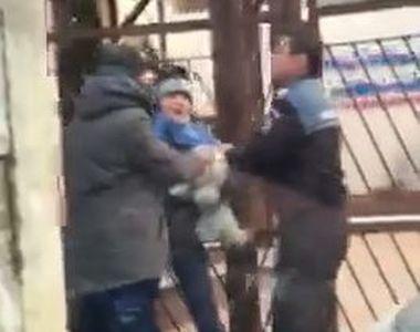 Un politist trage de un copil cu un caine in brate. Mama lui era de fata. Imagini...