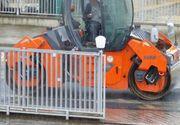 Hunedoara: Mai multi muncitori asfalteaza de zor pe o ploaie torentiala.