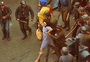 """Cine e """"doamna in rochie albastra"""" de la mineriada din 1990? Imaginea cu ea flancata de muncitori a facut inconjurul lumii, insa pana acum nimeni nu a stiut cine este aceasta femeie"""