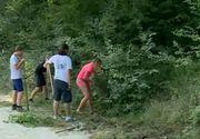 Intr-un sat din Romania, voluntari francezi strang gunoaiele. In acest timp, localnicii stau pe marginea santului si ii privesc