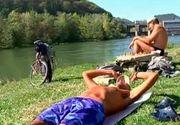 Plaja in ultima zi de septembrie. Oamenii s-au scaldat in rau si s-au relaxat la soare