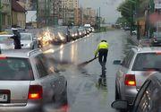Respect! Un politist din Brasov, fotografiat in timp ce matura carosabilul, pe ploaie, dupa un accident