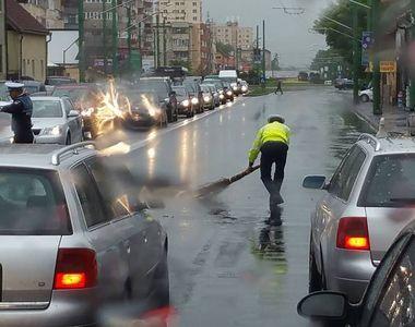 Respect! Un politist din Brasov, fotografiat in timp ce matura carosabilul, pe ploaie,...
