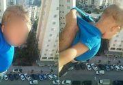 Scene ireale! Motivul halucinant pentru care acest barbat si-a tinut copilul atarnat pe geam de la etajul al 15-lea