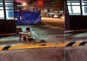 Imaginea care te lasă mut! Un băiețel fără adăpost își face temele la lumina unui fast-food