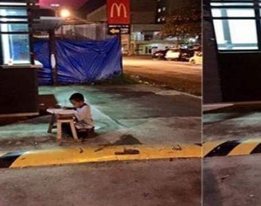 Imaginea care te lasă mut! Un băiețel fără adăpost își face temele la lumina unui...
