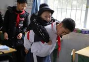 Un copil își duce prietenul bolnav, la școală, în spate