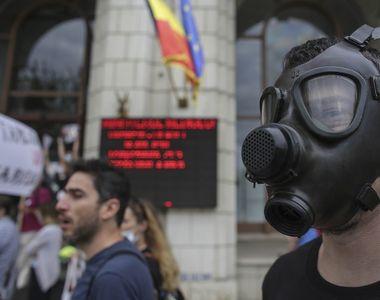 Zeci de persoane, unele cu măşti de gaze, au protestat în faţa Ministerului Mediului,...
